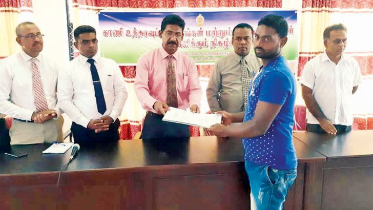 Ampara Additional District Secretary K. Vimalanathan hands over a title deed to a resident. Picture by Addalaichenai Central Corr.