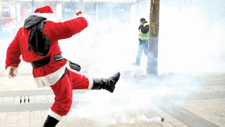 A protester dressed as Santa Claus kicks a tear gas canister away as smoke is released into the air during clashes in the French capital this afternoon.