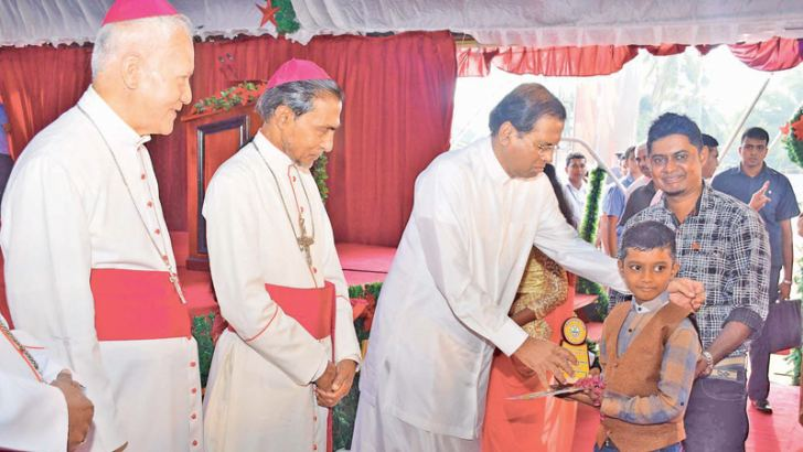 President Maithripala Sirisena presents a prize to a child at the state Christmas festival 2018 in Mannar.  Picture courtesy President's Media Division