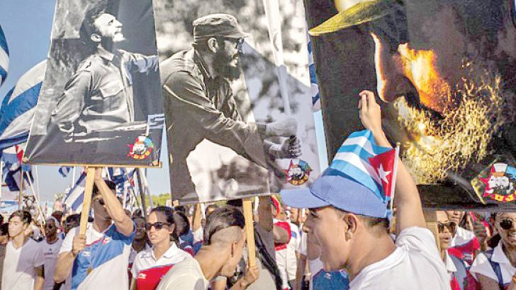 Students hold Cuban flags and pictures of revolutionary leader Fidel Castro during a parade in Havana.