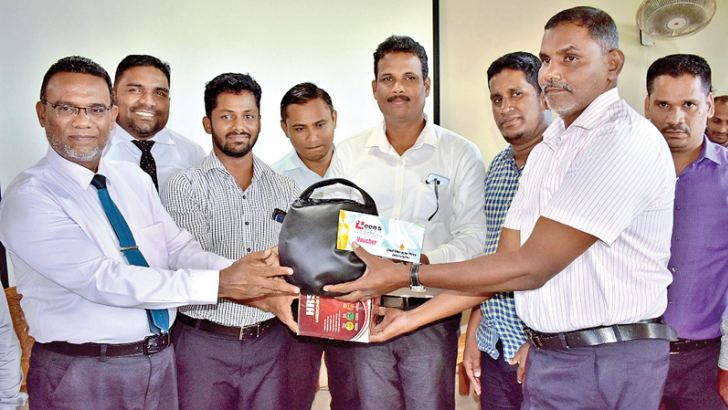 A principal receives a set of sports gear from the chief guest.