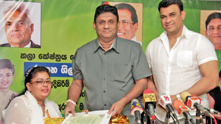 Minister Sajith Premadasa presents the deed of the house to Anusha Sonali, while Non-Cabinet Minister Ranjan Ramanayake looks on. Picture by Nissanka Wijeratne