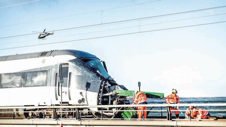 Men work at the accident site next to a passenger train standing on the rails in Nyberg, Denmark.