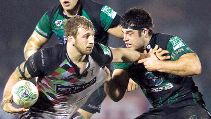 Ronan Loughney (right) tackles Harlequins and England flanker Chris Robshaw in 2012.