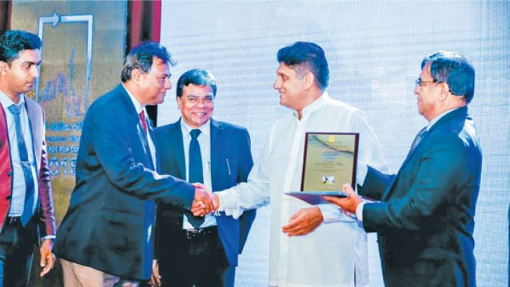 Officials of Sripalie Contractors receiving the award from Minister of Housing and Construction Sajith Premadasa.