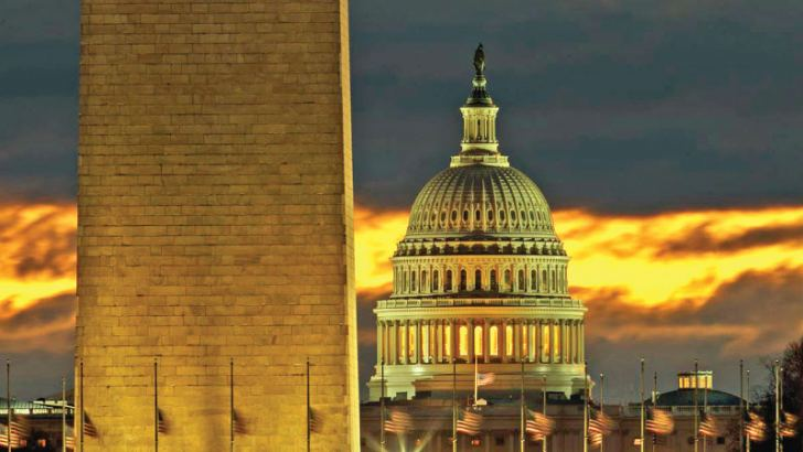 The U.S. Capitol dome is seen past the base of the Washington Monument just before sunrise in Washington.