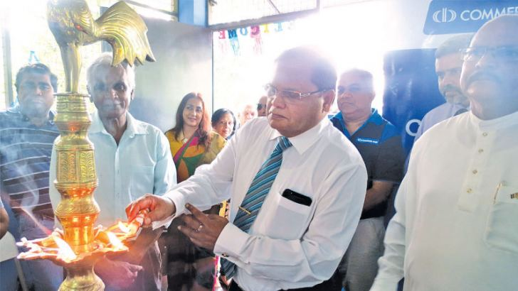 Commercial Bank Chairman Dharma Dheerasinghe lights the traditional oil lamp at the opening of the vocational training centre.