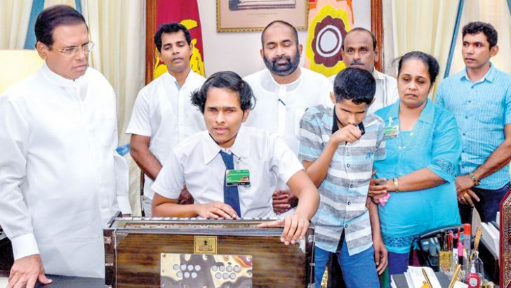 President Maithripala Sirisena looks on as Sanjali Nayantara plays the harmonium he presented her. Her parents, brother Gimhana Nayanajith and Parliamentarian Ranjith Siyambalapitiya are also present. Picture courtesy President's Media Division