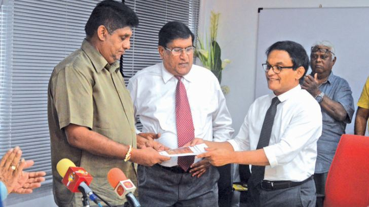 Presentation of the research document on Condominium development to Minister Sajith Premadasa. From Left: Housing, Construction and Cultural Affairs Minister Sajith Premadasa, Chairman of the Condominium Management Authority C. A. Wijeyeweere, Senior Lecturer in Architecture and Architectural Science, Moratuwa University Dr. Upendra Rajapaksha.