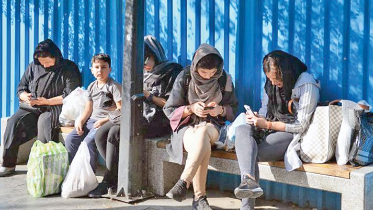 Iranian women look at their mobile phones outside the Tehran Grand Bazaar on October 2, 2018. AFP