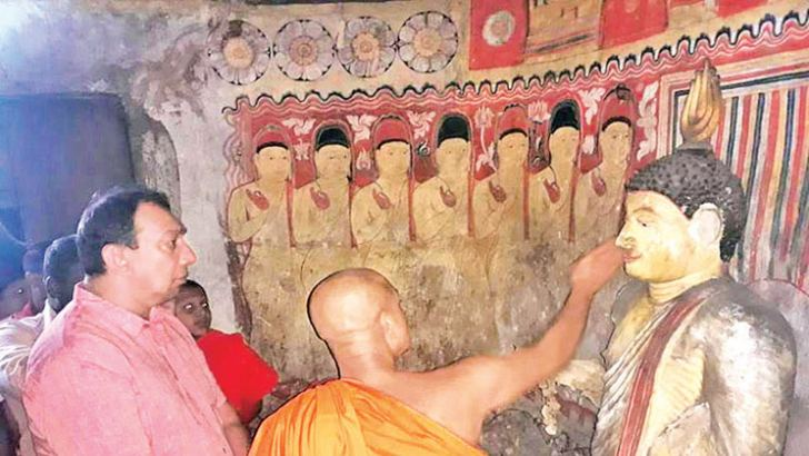 A monk shows State Tourism and Wildlife Minister Ranjith Aluvihare the extent of damage.