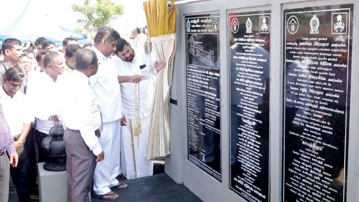 Minister Sajith Premadasa unveiling the plaque at the model village.