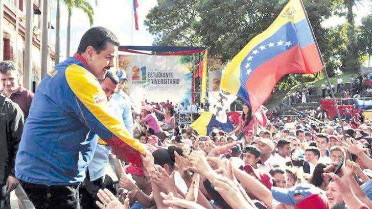 Venezuela's President Nicolas Maduro greets supporters during a rally on University Student Day in Caracas. - AFP