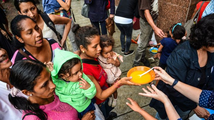 Women and children wait in line for food in Caracas, Venezuela.