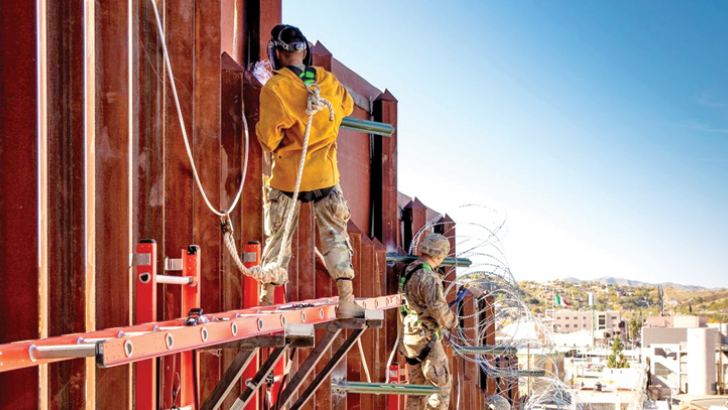 Members of the Army's 104th Engineer Construction Company install concertina wire on the border wall east of the Port of Nogales in Arizona.