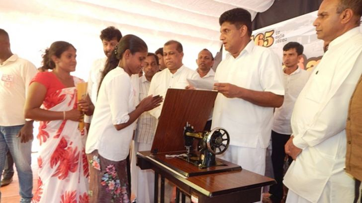 Minister Sajith Premadasa providing a sewing machine to a beneficiary after opening the model village.