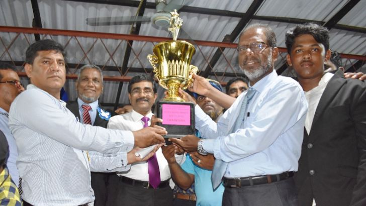 The Guest of honour Eastern Province Chief Ministry's Secretary U.L.A. Azees handing over the trophy to the Arafa House President  J. Fahir and house captain (Boys) M.A.Sasni Ahamed.