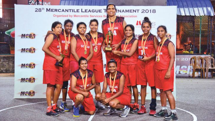 Champion Seylan Bank women's basketball team with the trophy