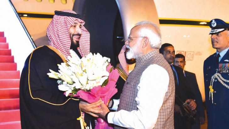 Indian Prime Minister Narendra Modi welcoming Saudi Crown Prince Mohammed bin Salman (L) at an airport in New Delhi. - AFP