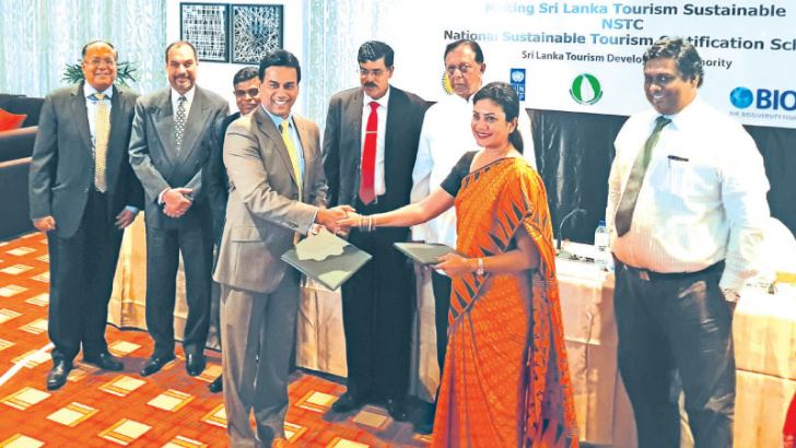 Chairman Sri Lanka Tourism Development Authority, Kishu Gomes and UNDP, Policy and Design Specialist UNDP, Tharuka Dissanaike, exchanging the agreement in the presence of the Minister of Tourism Development Wildlife and Christian Affairs, John Amaratunga and Director General SLTDA, Upali Ratnayake.