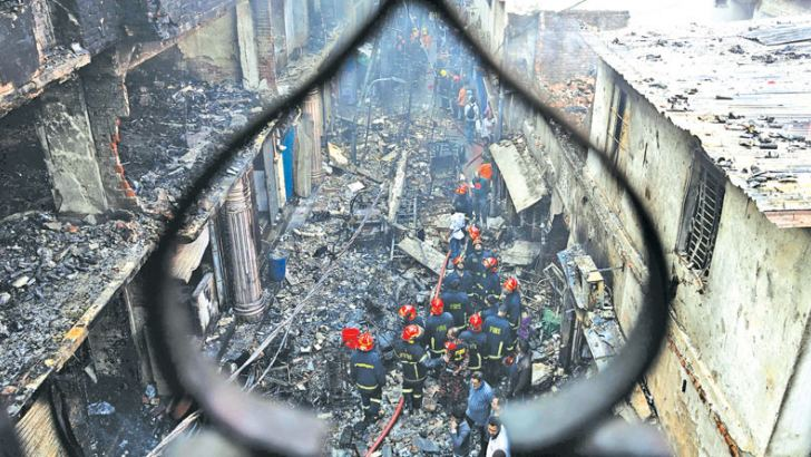 Firefighters are seen at the scene of a fire in Dhaka yesterday. - AFP