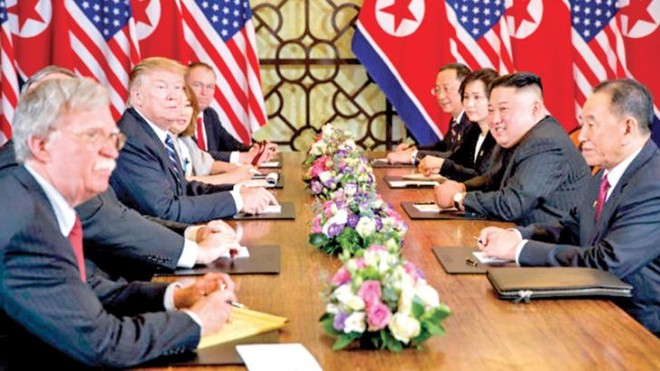 US President Donald Trump speaks during a meeting with North Korean leader Kim Jong Un  on February 28, 2019 in Hanoi. At front right is senior North Korean ruling party official and former intelligence chief Kim Yong Chol. At left is US National Security Adviser John Bolton.