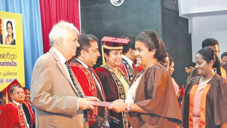 A teacher receiving her diploma certificate from Prime Minister Ranil Wickremesinghe at Temple Trees yesterday. Education Minister Akila Viraj Kariyawasam looks on.