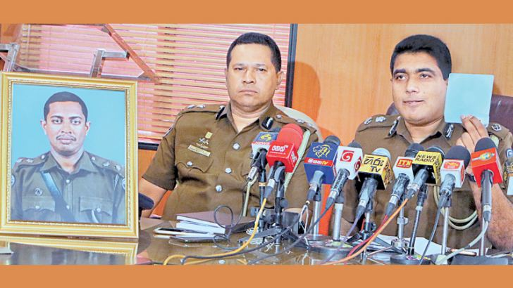 (Motor Traffic and Road Safety) DIG Ajith Rohana with a portrait of the victim Inspector at yesterday's press conference. Picture by Saman Sri Wedage