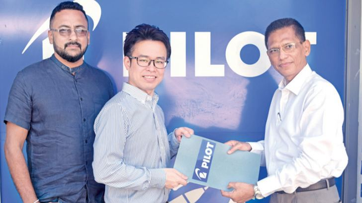 CH17  Loyalty CEO exchanging documents with Hiroki Kisaichi. s  Ravi Perera Director of WIL (Pvt) Ltd look on