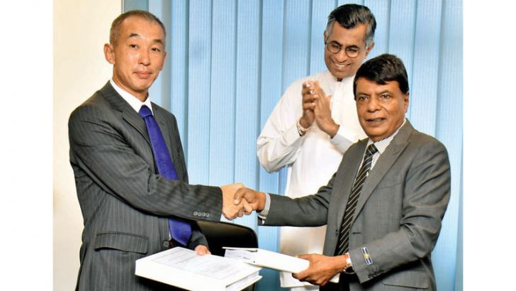 Minister Patali Champika Ranawaka looks on as Oriental Consultation Global General Manager Ryohei Ishii and Megapolis and Western Development Ministry Secretary N. Rupasinghe exchange copies of the agreement yesterday.  Picture by Gayan Pushpika