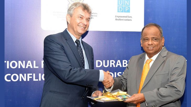 UNDP Resident Representative in Sri Lanka Jorn Sorensen presenting the copy to National Policies, Economic Affairs, Resettlement and Rehabilitation, Northern Province Development, Vocational Training and Skills Development and Youth Affairs Ministry Secretary, V. Sivagnanasothy,