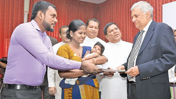 Prime Minister Ranil Wickremesinghe presents a computerised birth certificate to the parents of a new born, at the launch.