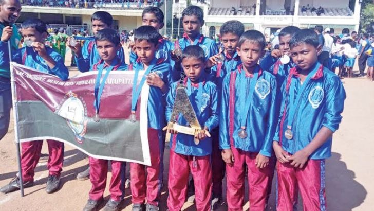 Champion Akkaraipattu Government Boys Vidyalaya Grade 3 kids team with their trophy and medals.