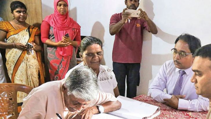 An elderly couple registering their marriage before Marriage Registrar Sumeda Rathnapala.