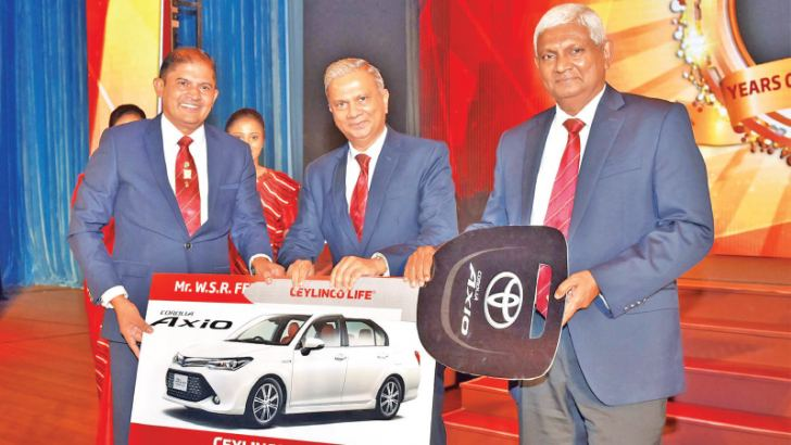 W. S. R. Fernando of Ceylinco Life's Negombo 01 branch (left) receives his Toyota Axio car from the Company's Chairman  R. Renganathan (right) and Managing Director/CEO  Thushara Ranasinghe