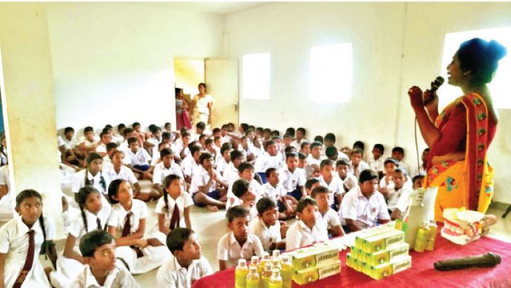 Schoolchildren of Sunandopanada Maha Vidyalaya, Moratuwa listen intently to the benefits of Ayurveda herbs in their toothpaste