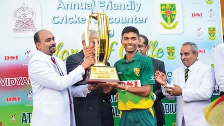 Winning Captain Gimhana Ashirwadha of St.Aloysius College, receiving the trophy from Prasanna Seneviratna, the principal of Vidyalokha College in the presence of his principal Nayanapria Perera.
