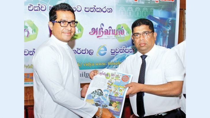 ANCL Chairman Krishantha Cooray presenting a copy of the 'Vidya' supplement to Science, Technology and Research non-Cabinet Minister Sujeewa Senasinghe at the Lake House premises on Tuesday. Picture by Saliya Rupasinghe.