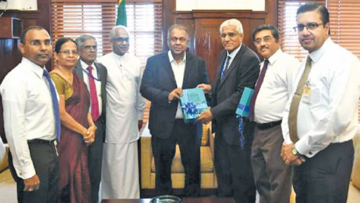 Governor CBSL,  Dr.  Indrajit  Coomaraswamy,  presenting  the  Annual  Report  2018 to Mangala Samaraweera, the Minister of Finance. State Minister of Finance, Eran Wickramaratne, Secretary to the Ministry of Finance, Dr. R.H.S.Samaratunga, Senior Deputy Governor, Dr. P. Nandalal Weerasinghe, Assistant  Governor, Swarna Gunaratne, Acting Director  of  Economic  Research  Dr.  Chandranath  Amarasekara, and  Dr. P. K. G. Harischandra, Additional Director of Economic Research look on.