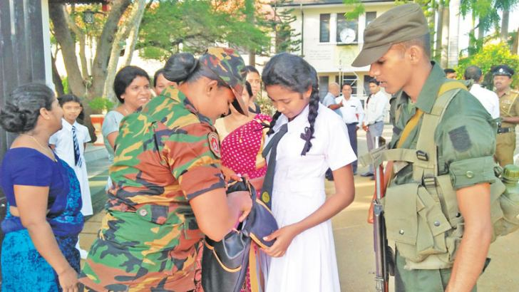 Schools opened yesterday after the deadly Easter Sunday terror attacks which claimed over 250 lives. Security Forces personnel are seen inspecting the school bags of children as they enter Anuradhapura Central College. Picture by Amila Prabath Wanasinghe