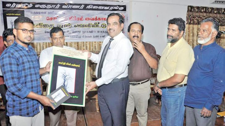 Razeem Hameed receives a copy of the book from Chief Guest AHM Ansar