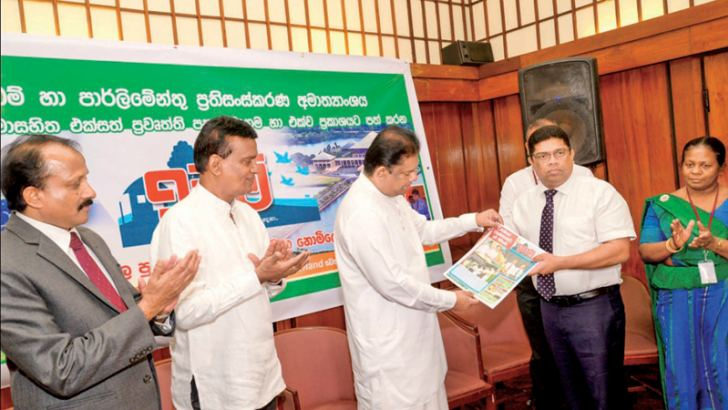 The first copy of the 'IDAM' (Lands) publication is presented to Lands and Parliamentary Reforms Minister Gayantha Karunathilaka by Lake House Chairman Krishantha Cooray. Deputy Minister Edward Gunasekara, Secretary to the Ministry W.H. Karunaratne and Senior Management of the Lake House were present. Picture by Shan Rupassinge