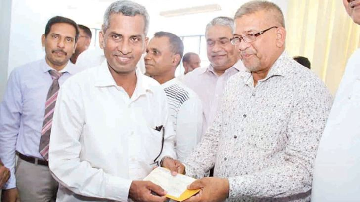 A beneficiary receives compensation from Deputy Minister Abdullah Mahrooff.  Picture A.B. Abdul Gafoor