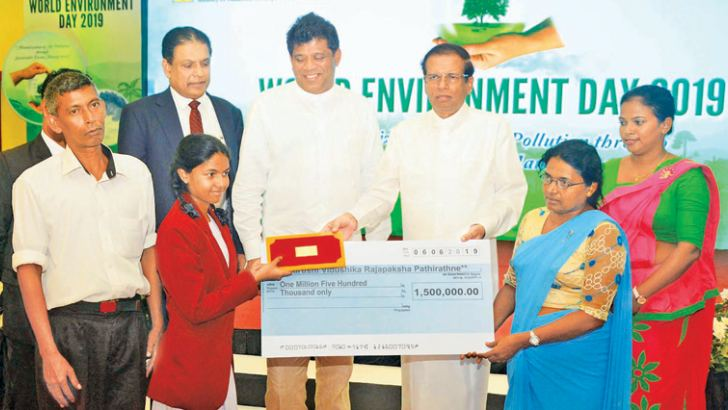 President Maithripala Sirisena presented a cheque for over Rs 1.5 million to Vidhushika Rajapaksa Pathiratne, a student of Sumana Balika Vidyalaya, Ratnapura, for inventing  an alternative to plastic lunch sheets, at the World Environment Day celebrations held at the BMICH yesterday. Picture by Sudath Malaweera.
