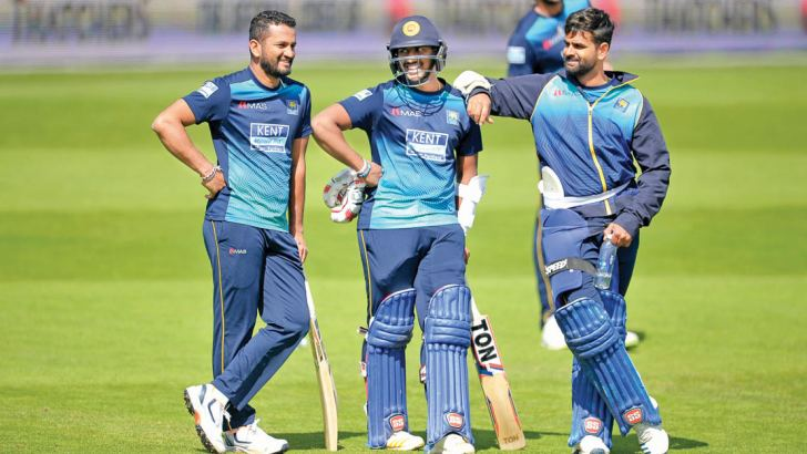 Sri Lanka captain Dimuth Karunaratne (on left) has a word with the youngest member of the Sri Lanka World Cup squad 21-year-old Avishka Fernando (in helmet) with Lahiru Thirimanne watching during practice at Headingley, Leeds on Thursday.