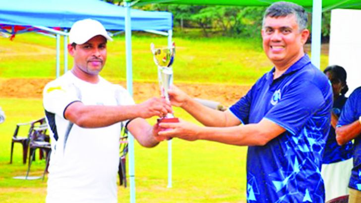 The Captain of the Champion Accounts Branch team,Sagara Chaminda receiving the Champion Trophy from Tissa Karunaratne. the Government Agent, Kandy
