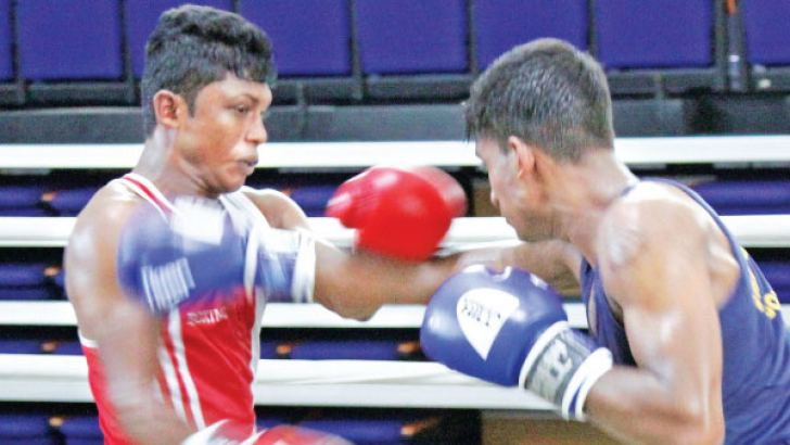 Police's P.A.R. Prasanna (red) parries a blow from Army Reds' D.M. Dassnayake on his way to a unanimous points win in the Bantam weight semifinal of the Intermediates boxing tournament at Royal MAS Arena yesterday. (Pix by Chaminda Niroshana)