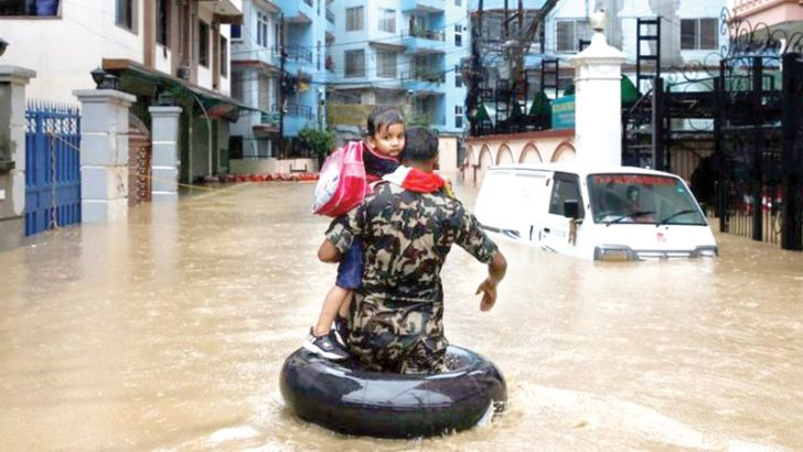 A member of Nepalese army carrying a child walks along the flooded colony in Kathmandu, Nepal on Saturday.