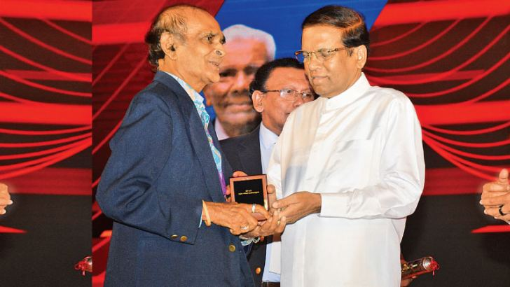 Veteran sports journalist Elmo Rodrigopulle receiving the 'Kreeda Prabha' award from the chief guest  President Maithripala Sirisena. The award was presented in recognition of long term service for sports journalism. Pictures by Sudath Malaweera
