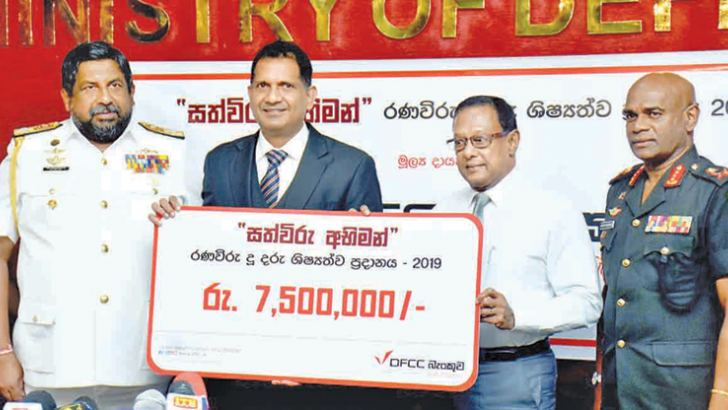 DFCC Bank's Liabilities and Trade Business Development Vice President Anton Arumugam handing over the scholrship fund sponsorship cheque of Rs 7.5 mn to Defence Secretary Gen.Shantha Kottegoda. Chief of Defence Staff Admiral Ravindra Wijegunaratne and Army Commander Lt. Gen. Mahesh Senanayake look on.  Picture by Gayan Pushpika